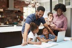 母亲抱着婴孩,父亲帮助有家庭作业的孩子 免版税库存照片