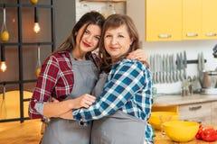 母亲拥抱厨房时间乐趣的女儿债券 免版税图库摄影