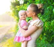 母亲拥抱和亲吻小女儿画象户外 免版税库存图片