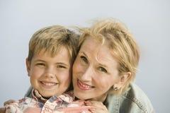 母亲拥抱的儿子画象户外 免版税库存照片