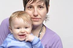 母亲拿着微笑的子项 免版税库存照片
