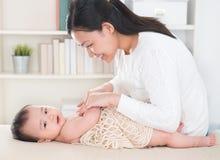 母亲按摩婴孩 图库摄影