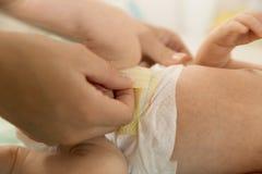 母亲换尿布到她新出生的婴孩 母性每日rou 图库摄影