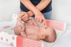 母亲换尿布到她的小婴孩 库存照片