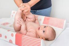 母亲换尿布到她的小婴孩 免版税库存图片