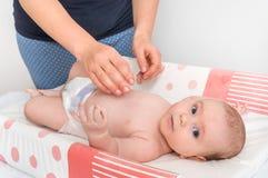母亲换尿布到她的小婴孩 库存图片