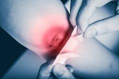 母亲提供紧急救护在创伤在儿子腿以红色斑点痛处 免版税库存图片