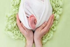 母亲握新生儿的脚用她的手、手指在脚,孕产照顾、爱和家庭拥抱,柔软 库存图片