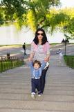 母亲攀登台阶的帮助孩子 库存照片