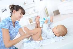 母亲改变的尿布九个月婴孩 库存照片