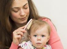 母亲教女儿掠过头发。 库存照片