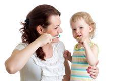 母亲教她女儿孩子刷牙 库存照片