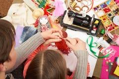 母亲教的女儿女孩编织,顶视图,缝合的辅助部件顶视图,裁缝工作场所,许多为针线, handm反对 免版税库存照片