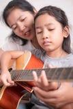 母亲教的女儿弹吉他 库存图片