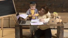 母亲教聪明的儿子画,在背景的黑板 听有注意的妈妈的男孩 母性概念 免版税库存图片