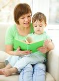 母亲是她的儿子的阅读书 图库摄影