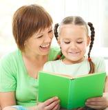 母亲是她的女儿的阅读书 库存图片