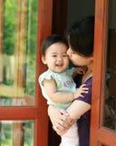 年轻母亲是抱着和亲吻她的站立在玻璃门的婴孩 库存图片