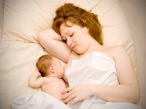 母亲是提供新出生的婴孩和dreami的乳房 库存照片
