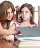 母亲检查她的女儿互联网活动 免版税图库摄影
