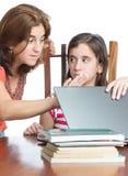 母亲检查她的女儿互联网活动 图库摄影