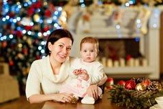 母亲浅黑肤色的男人拥抱白色的小逗人喜爱的胖的女婴 免版税库存照片