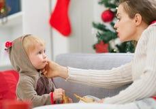 母亲清洁吃吃曲奇饼的被抹上的婴孩 图库摄影