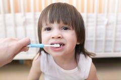 母亲清洗牙他可爱的小孩 免版税库存照片