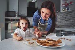 母亲烘烤与她的女儿在厨房里 库存照片