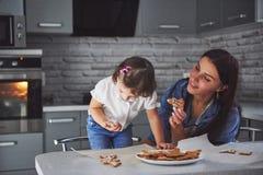 母亲烘烤与她的女儿在厨房里 库存图片