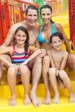 母亲父亲儿子女儿在水公园的儿童家庭 免版税库存图片