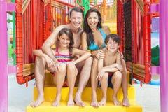 母亲父亲儿子女儿在水公园的儿童家庭 免版税库存照片