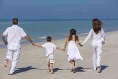 母亲父亲和跑在海滩的儿童家庭 免版税库存图片