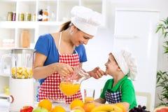 母亲用健康橙汁和她愉快的小孩 免版税图库摄影