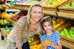 母亲用她的女儿买的桔子 免版税库存照片