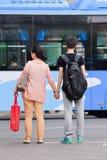 母亲由手采取她的儿子,当横渡, Kinming,中国时 库存照片