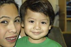 母亲画象和儿子愉快地微笑着 免版税库存照片