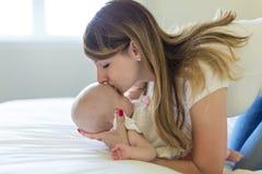 母亲画象有她的3个月大婴孩的在卧室 库存图片