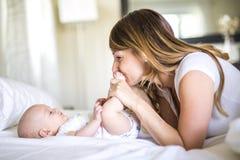 母亲画象有她的3个月大婴孩的在卧室 免版税库存图片