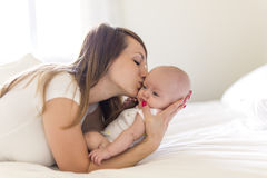 母亲画象有她的3个月大婴孩的在卧室 免版税图库摄影
