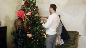 母亲的年轻愉快的快乐的家庭在圣诞老人装饰圣诞节的帽子、父亲和两个逗人喜爱的女儿穿戴了 影视素材