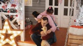 母亲的幸福家庭,父亲、女儿和狗获得乐趣在圣诞节门廊 股票录像