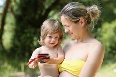 母亲的胳膊的愉快的矮小的微笑的孩子自然本底的 免版税库存照片