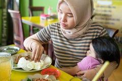 母亲的hijab的画象运载他的女儿的,当吃时 库存图片