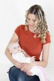 母亲看护她的婴孩 免版税库存照片