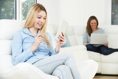 母亲研究膝上型计算机,十几岁的女孩使用数字式片剂 免版税库存图片