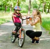 年轻母亲称赞她的女儿,学会骑自行车 图库摄影