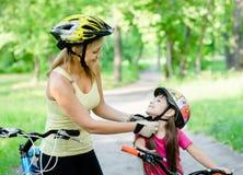 年轻母亲穿戴她的女儿的自行车盔甲 库存照片