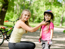 年轻母亲穿戴她的女儿的自行车盔甲 免版税库存图片