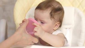 母亲给婴孩饮料水从玻璃,孩子的吃在孩子桌上 影视素材